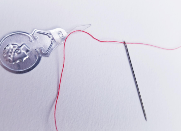 Image shows a needle threader with the needle and red thread attached on a light background.