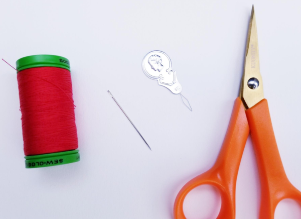 Image shows a spool of red thread, a needle, a needle threader, and scissors on a light background.