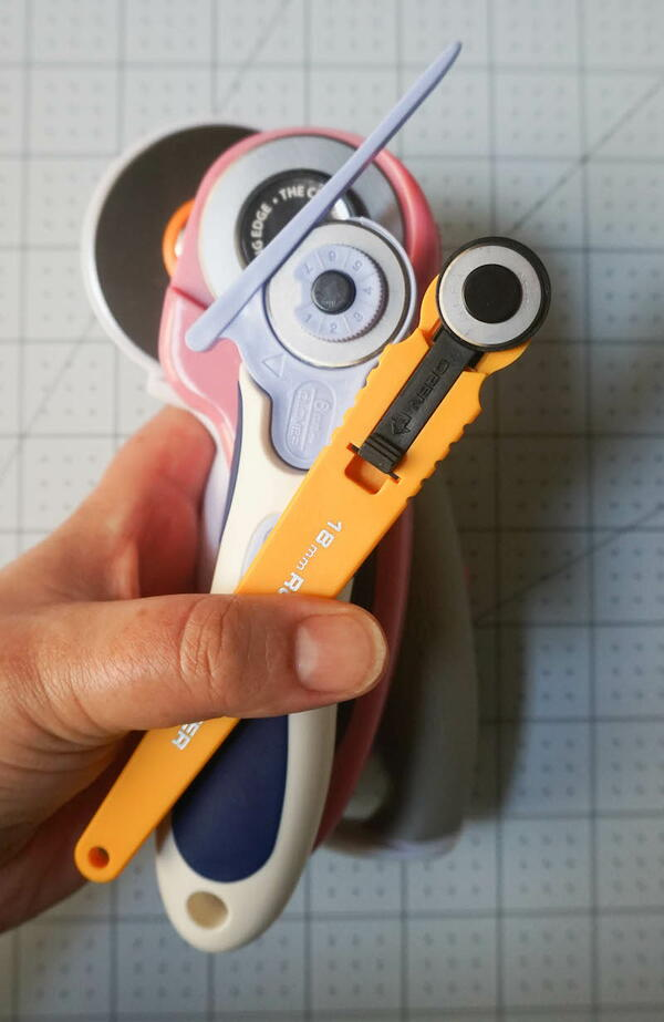 Image shows a hand holding multiple rotary cutters.