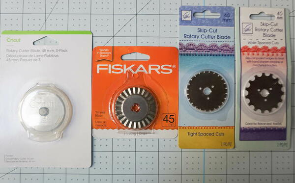 Image shows four different rotary cutter blades in packaging.