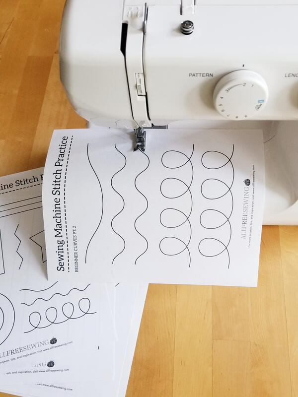 Image shows a sewing machine with a practice sheet being sewn.