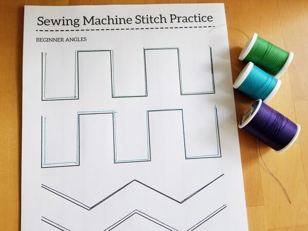 Image shows a sewn practice sheet with three spools of thread to the right of the sheet.