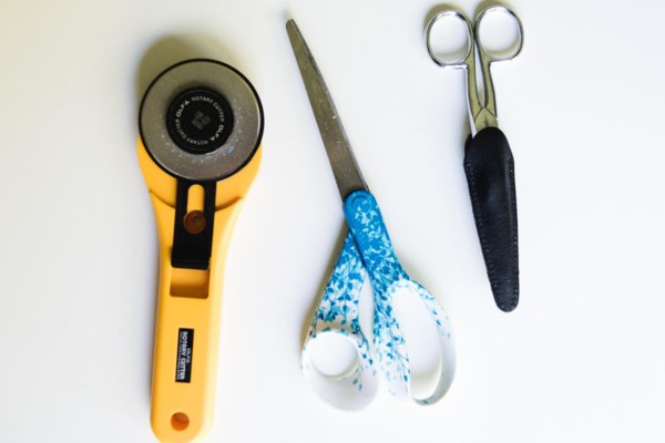Image of the tools shown left to right: rotary cutter, non-fabric scissors, and fabric scissors.