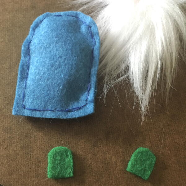 Image shows the blue felt body stuffed and sewn along with two green shoe pieces and the white beard for the DIY Gnome Ornament.