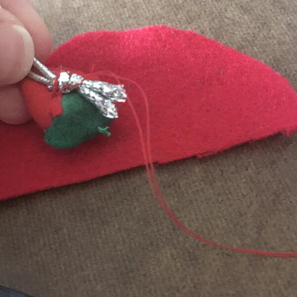 Image shows the half-circle of red felt, and the pincushion strawberry being sewn to the silver string for the DIY Gnome Ornament.