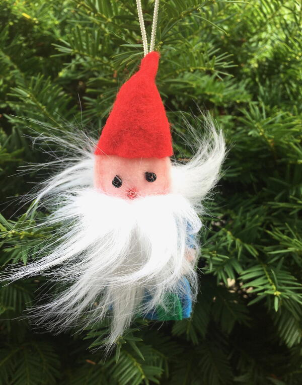 Image shows the finished gnome ornament hanging from an evergreen tree outside.