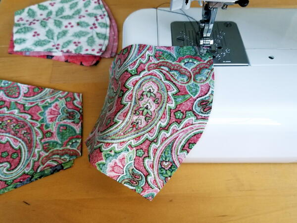 Image shows a sewing machine sewing two sides of a DIY face mask together. Off to the side, there are mask pieces sewn and waiting to be sewn.