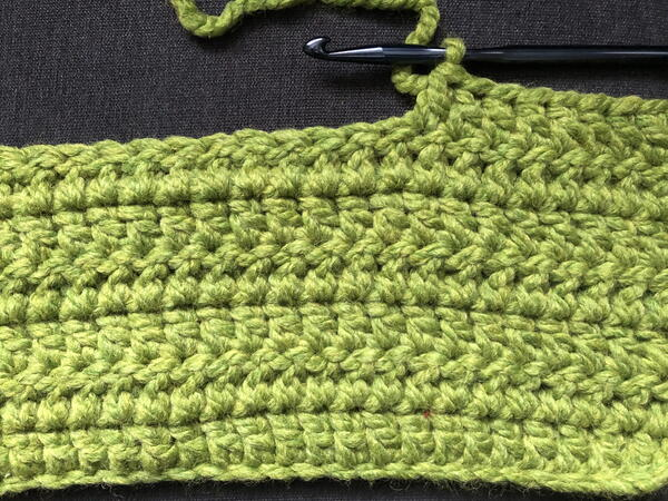 Image shows the start of a double crochet stitch blanket in green.