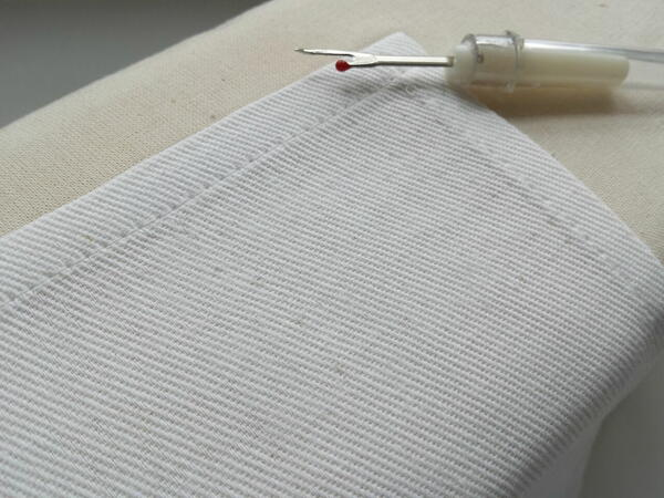 Image shows resulting look of fabric after removing stitches, pressing, and using a nail and spoon to help close up holes.