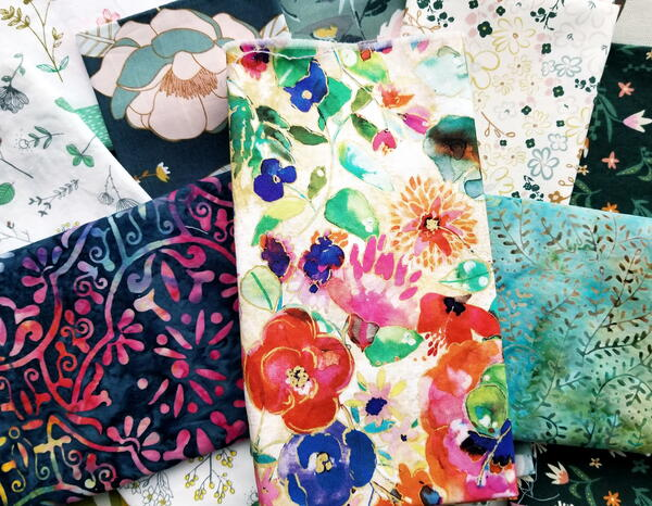 Image shows a stack of floral fabrics.