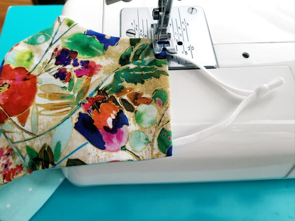 Image shows a sewing machine sewing the earloops onto the floral fabric face mask.