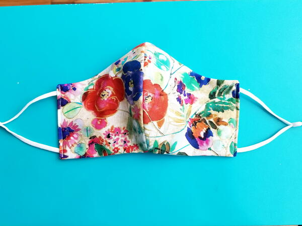 Image shows the finished floral fabric face mask.