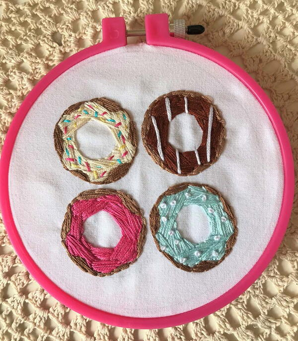 Example of hand embroidery: four hand embroidered donuts in a pink embroidery hoop.