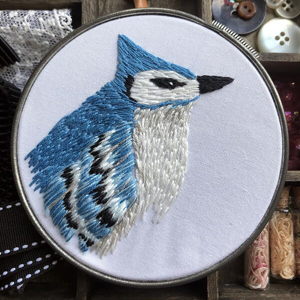 Example of needle painting embroidery: an intricate blue jay in a silver embroidery hoop.